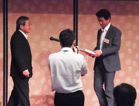 優良工務店表彰   安成総合保証代表からの記念盾の授与